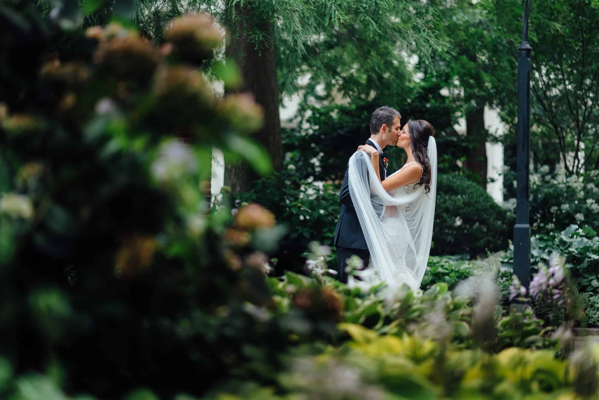 bride and groom embracing in a park before their summer Union Trust Wedding