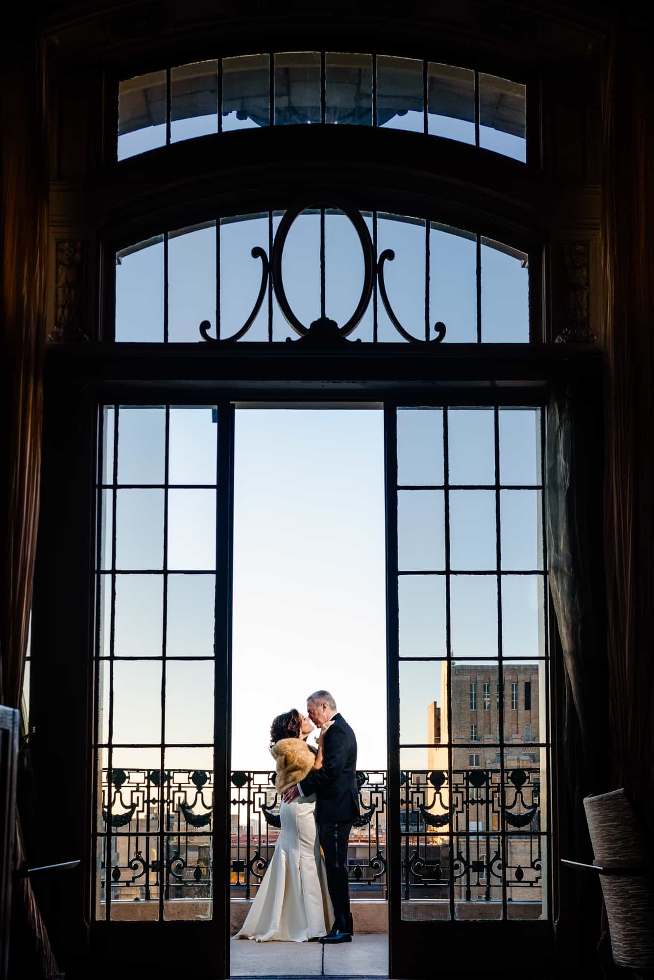 Bride and groom embracing in doorframe of the Bellevue Hotel