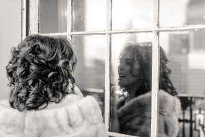 Bride apllying lipstick in window reflection
