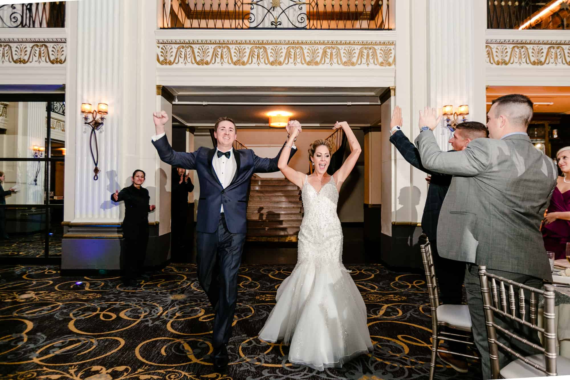Bride and groom raising their hands in the air while entering reception
