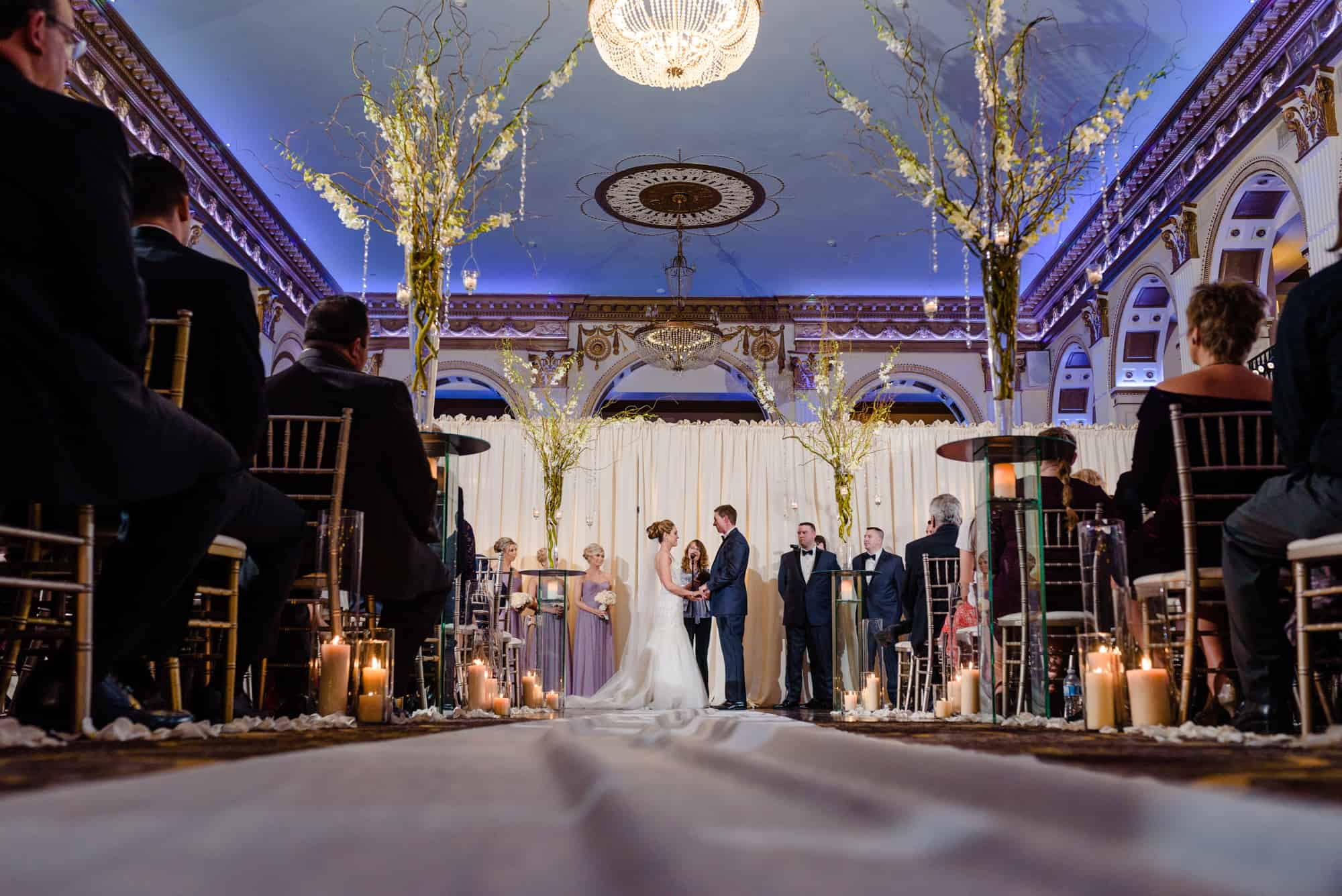 Bride and groom holding hands during ceremony at the Ballroom at the Ben