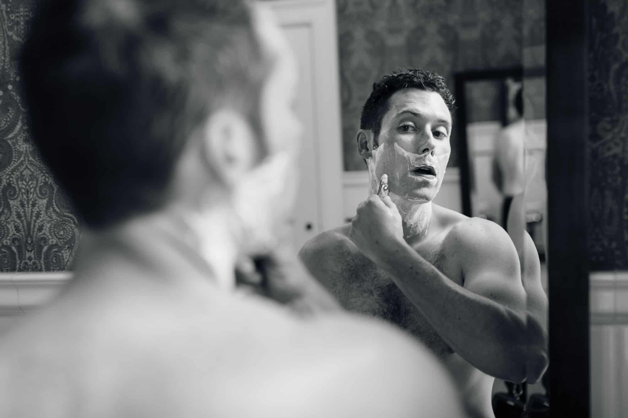 Groom shaving before wedding