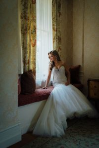 Bride sitting alone by a window at Cairnwood Estate