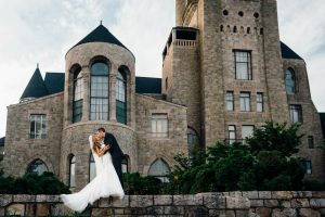 Romantic image of bride and groom kissing in front of mansion