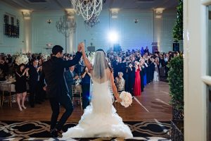 Bride and groom enter recption with hands raised in the air