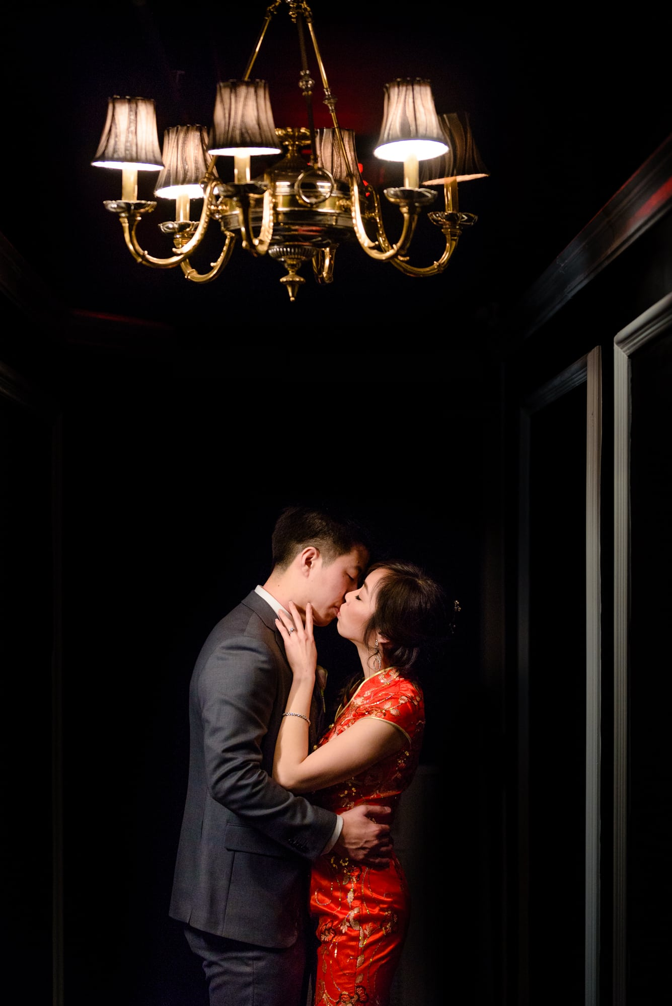 Bride and groom romantic kiss under light