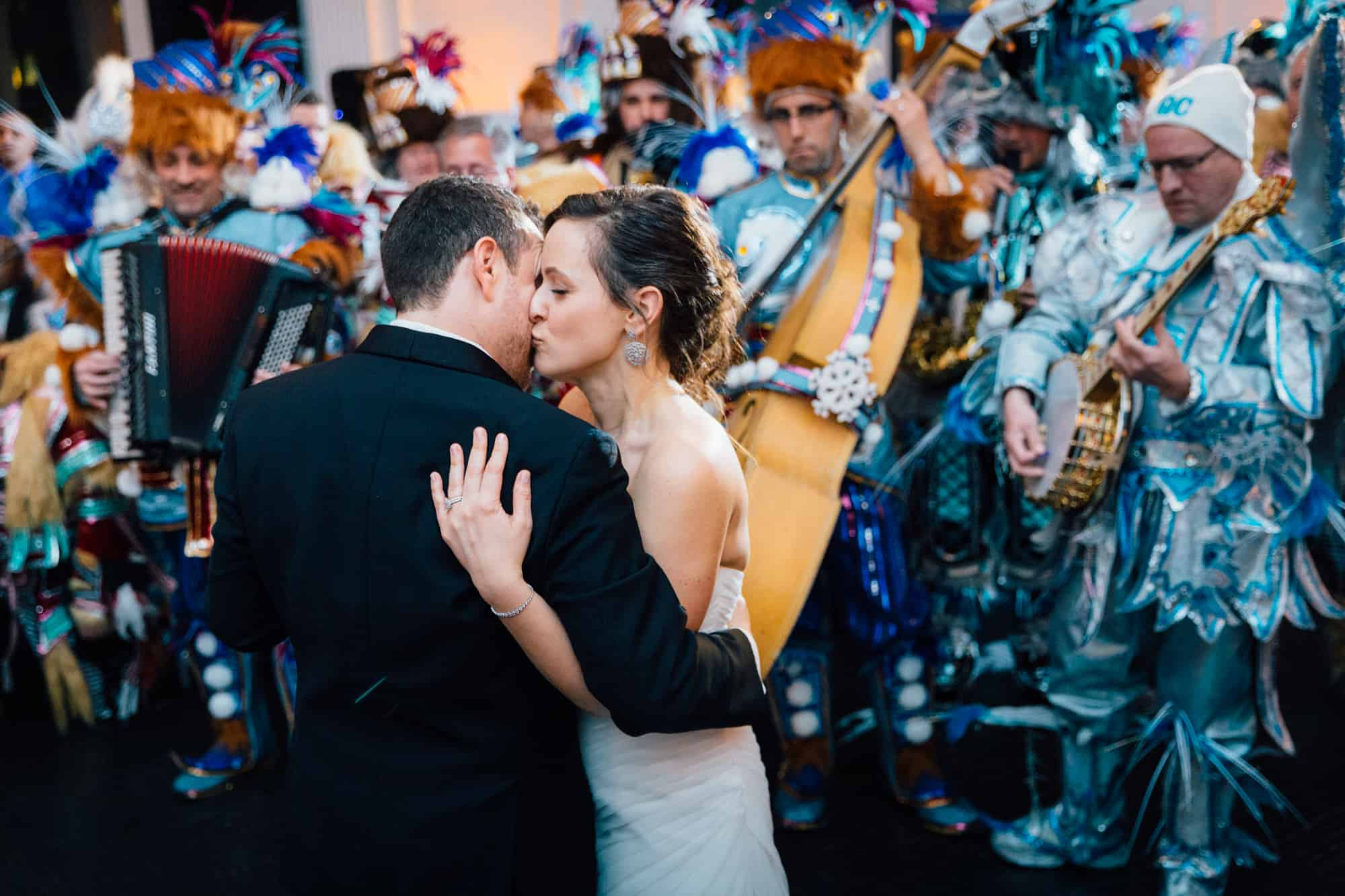 Bride and groom kissing in front of band