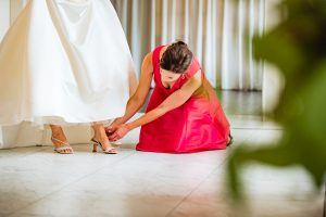 Bridesmaid in red dress helping bride put her shoe on