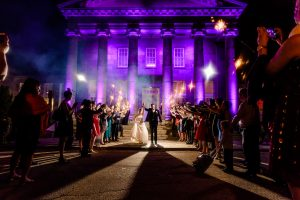 Bride and groom walking out of reception while guests hold sparklers