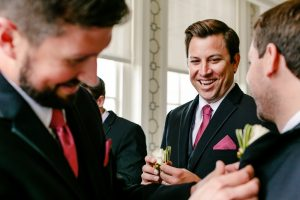 Groomsman laughing while holding white flower