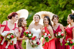 Bride and bridemaids in red dresses smiling
