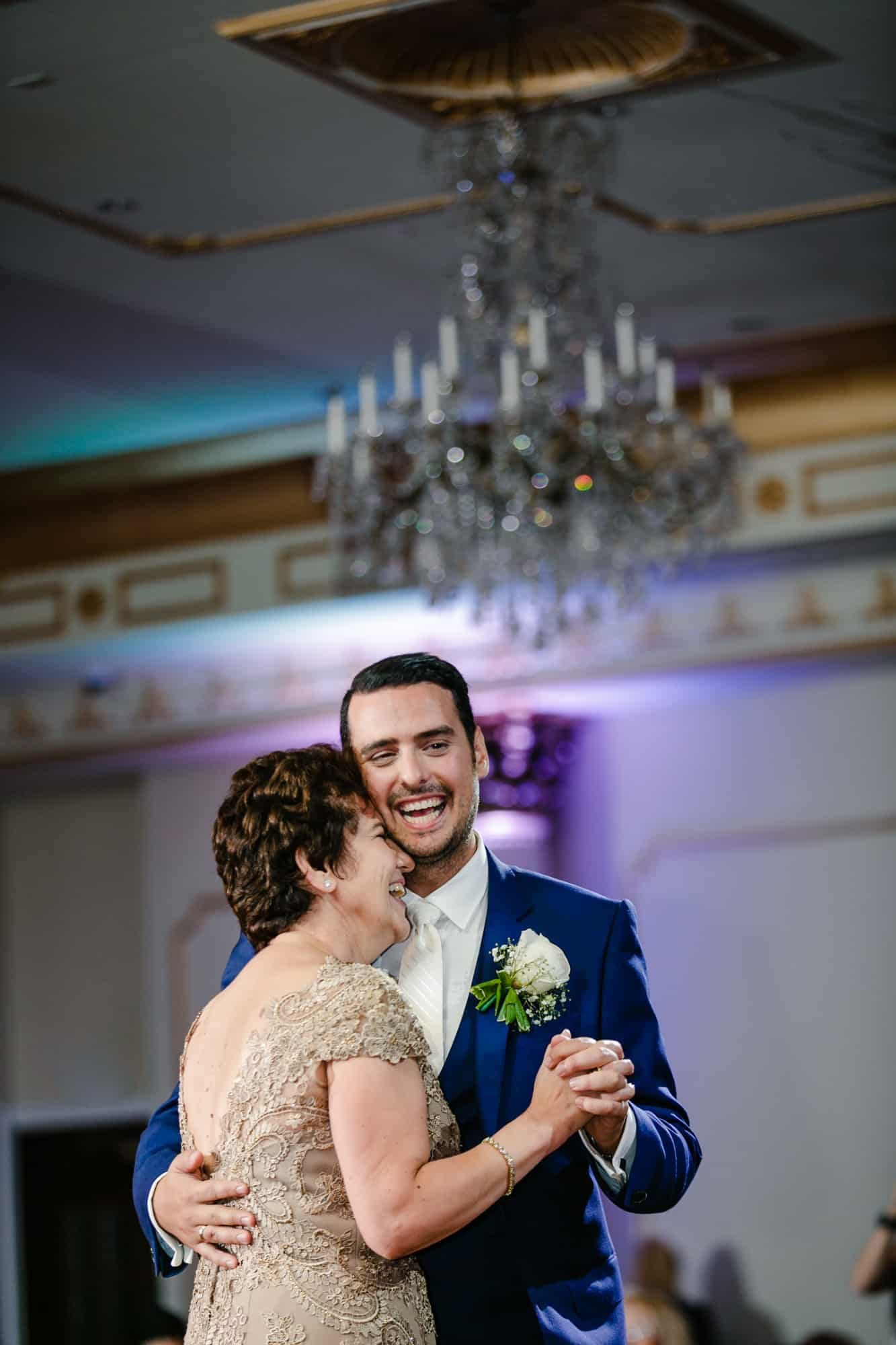 Groom smiling while dancing with mother