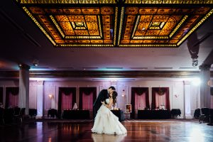 Bride and groom kissing in ballroom
