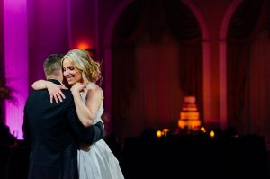 Bride and groom embrace while dancing