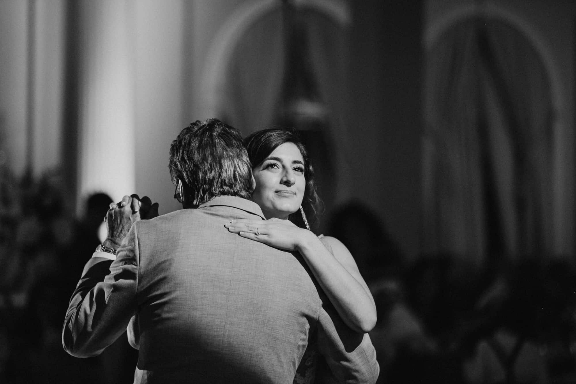 Black and white imagfe of bride dancing with father