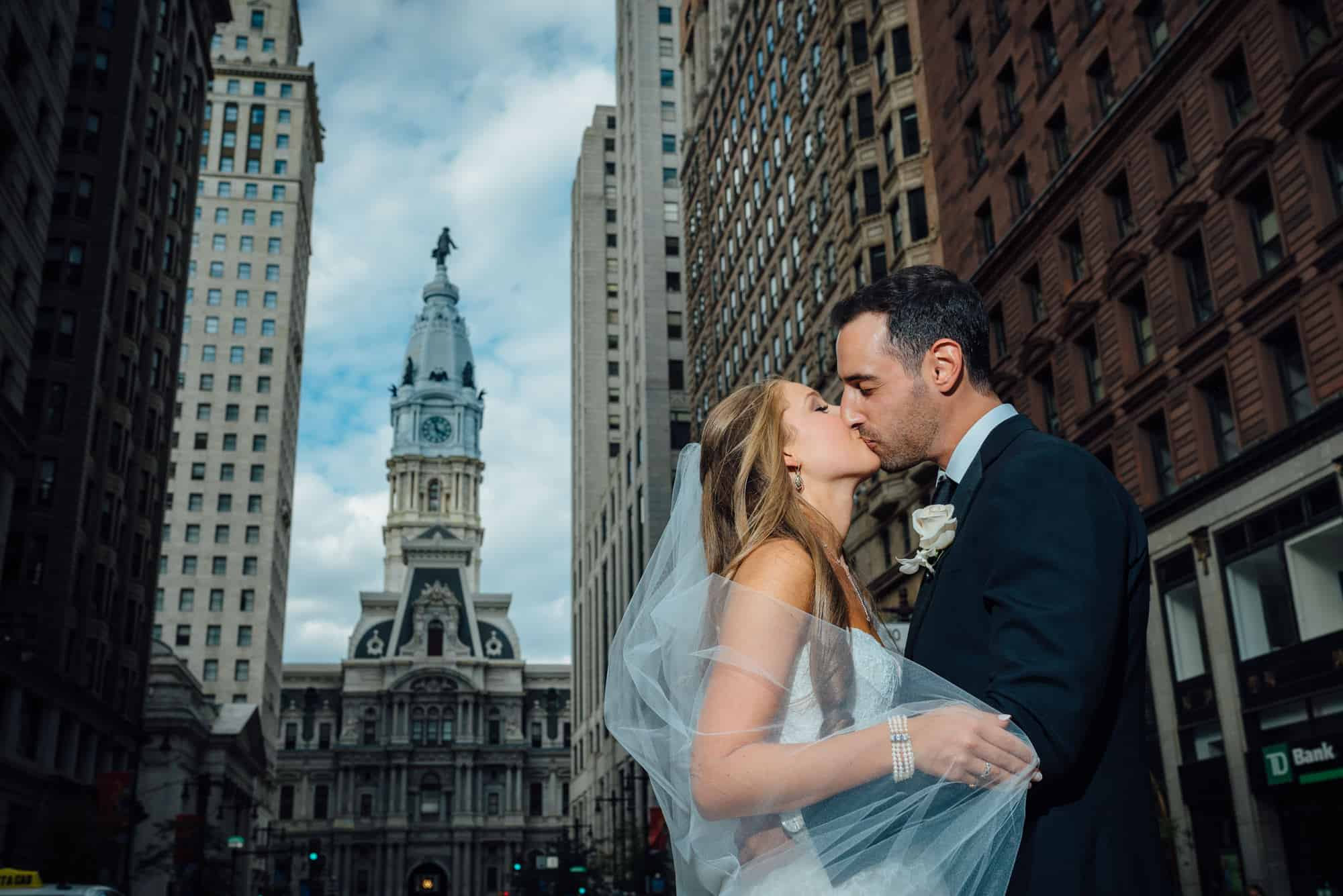 Bride and groom kissing in front of City Hall Philadelphia