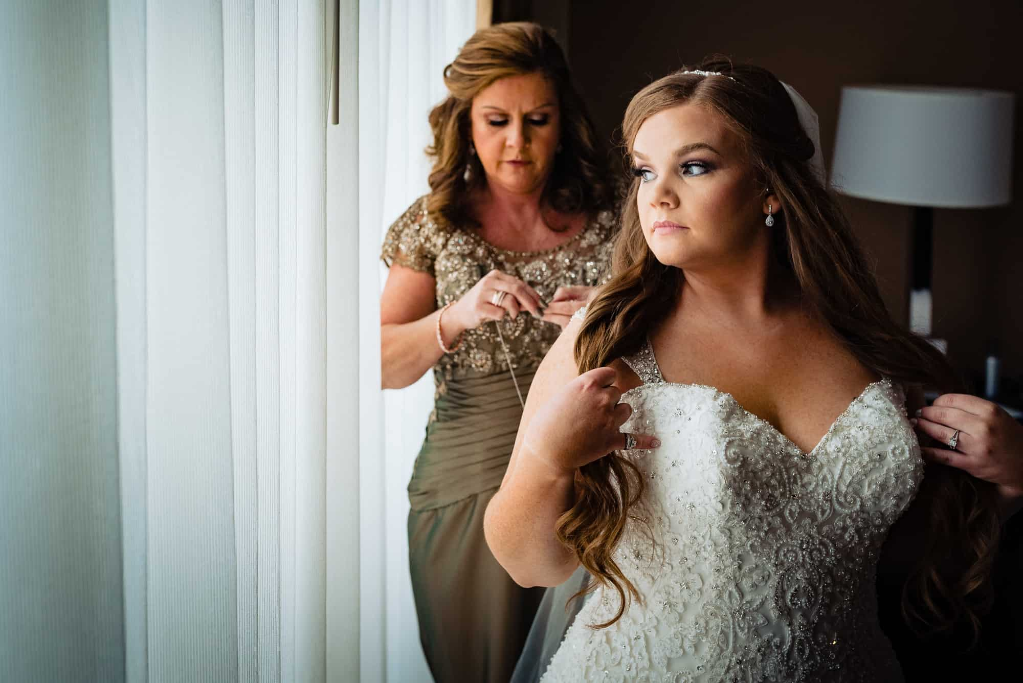 bride waiting for mother to put a necklace on her