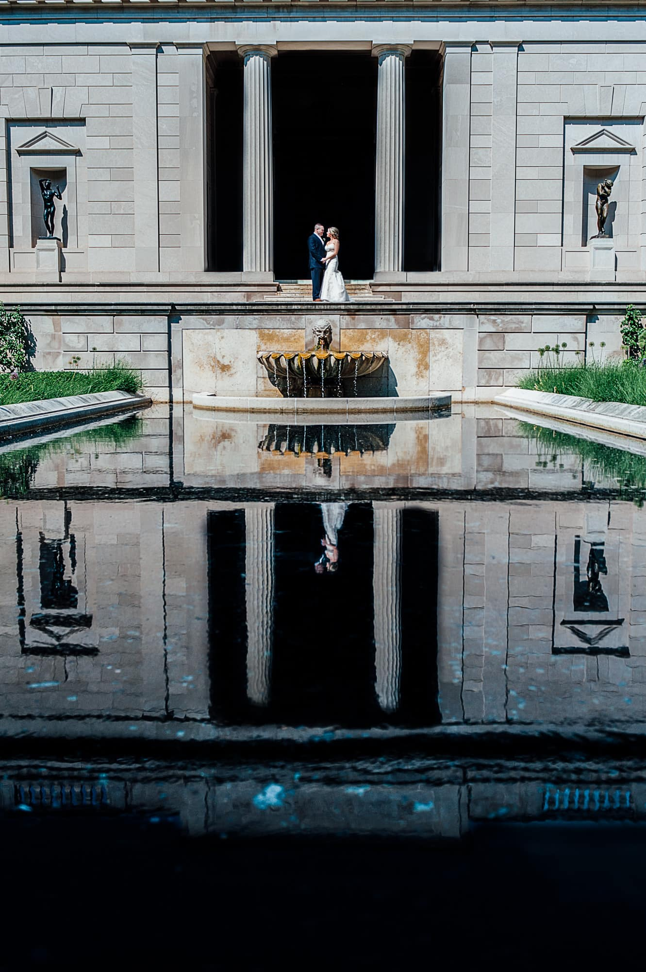 Bride and groom posing in front of Rodin Museum reflection pool