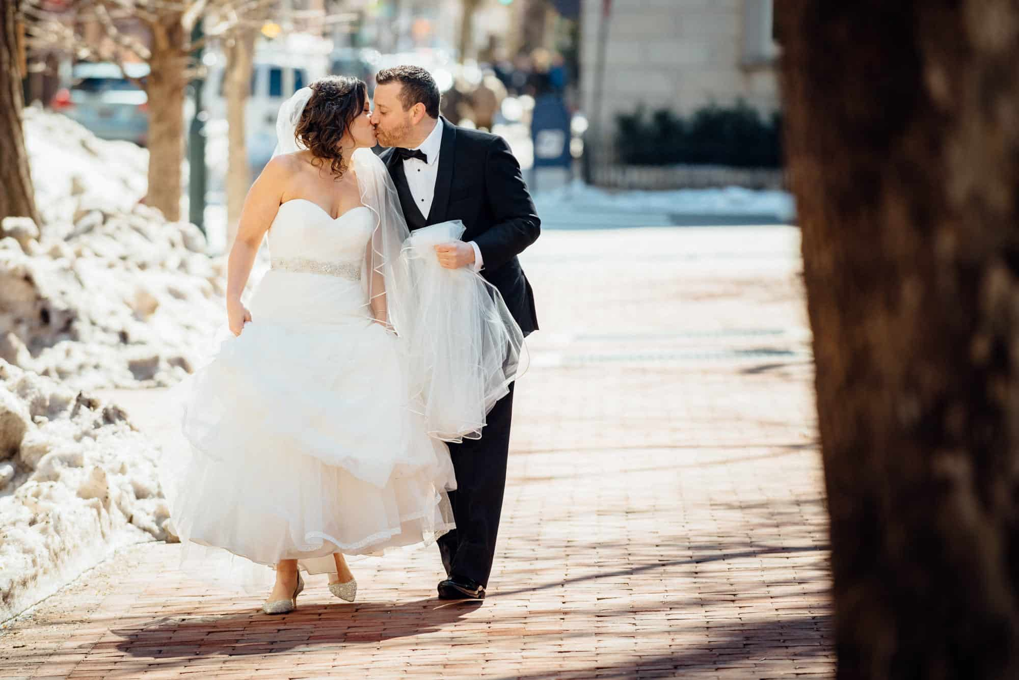 Bride and groom kissing on city street