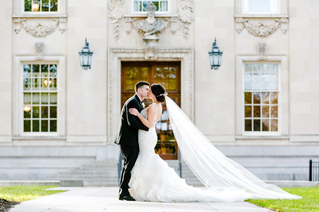romatic-fall-wedding-bride-groom-kissing-in-front-of-building