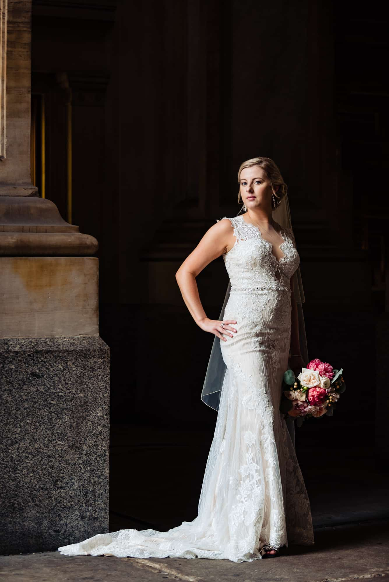wedding day, bride in lace Maggie Sottero gown with hand on hip