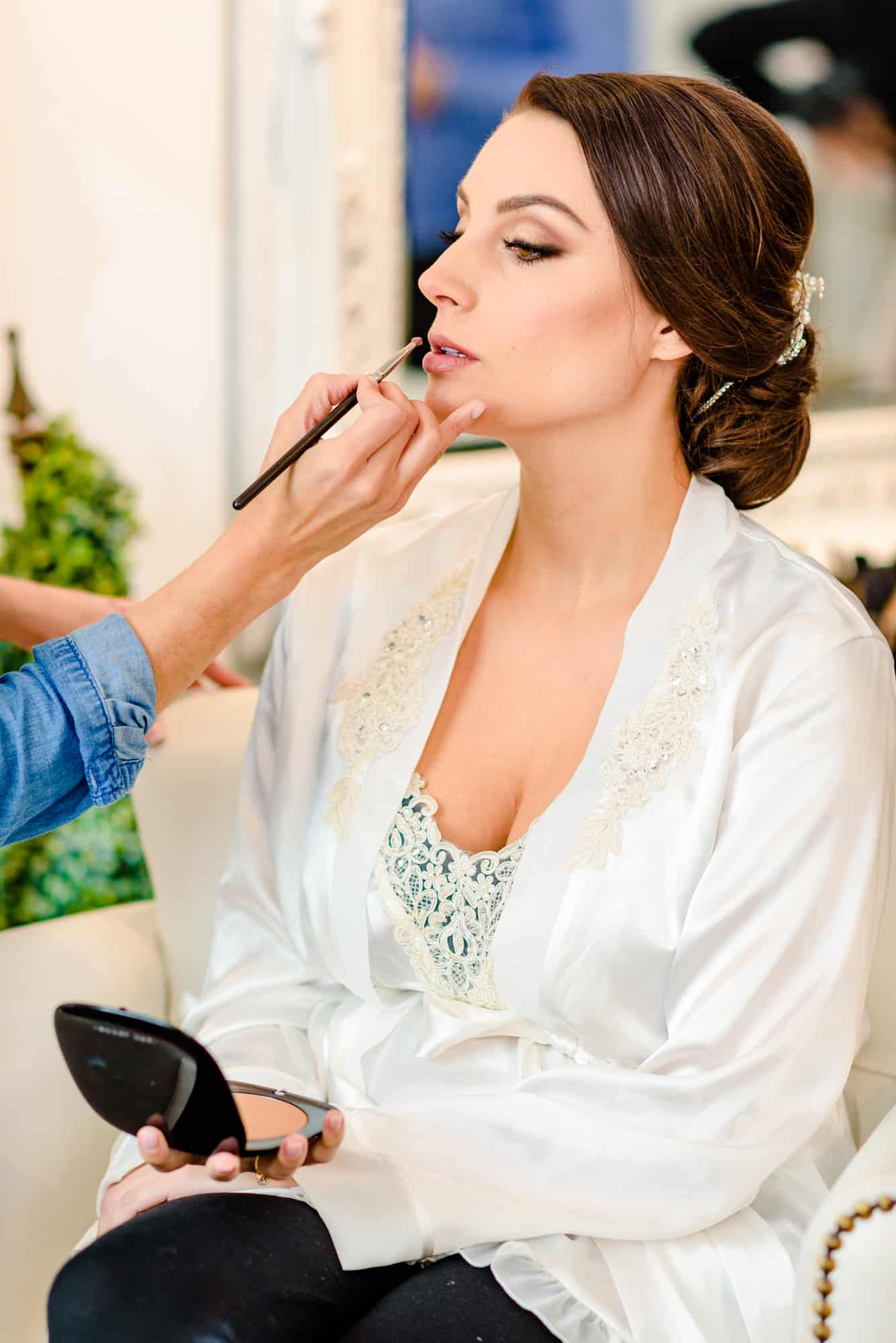 wedding makeup, artist applying lipgloss to bride while in robe