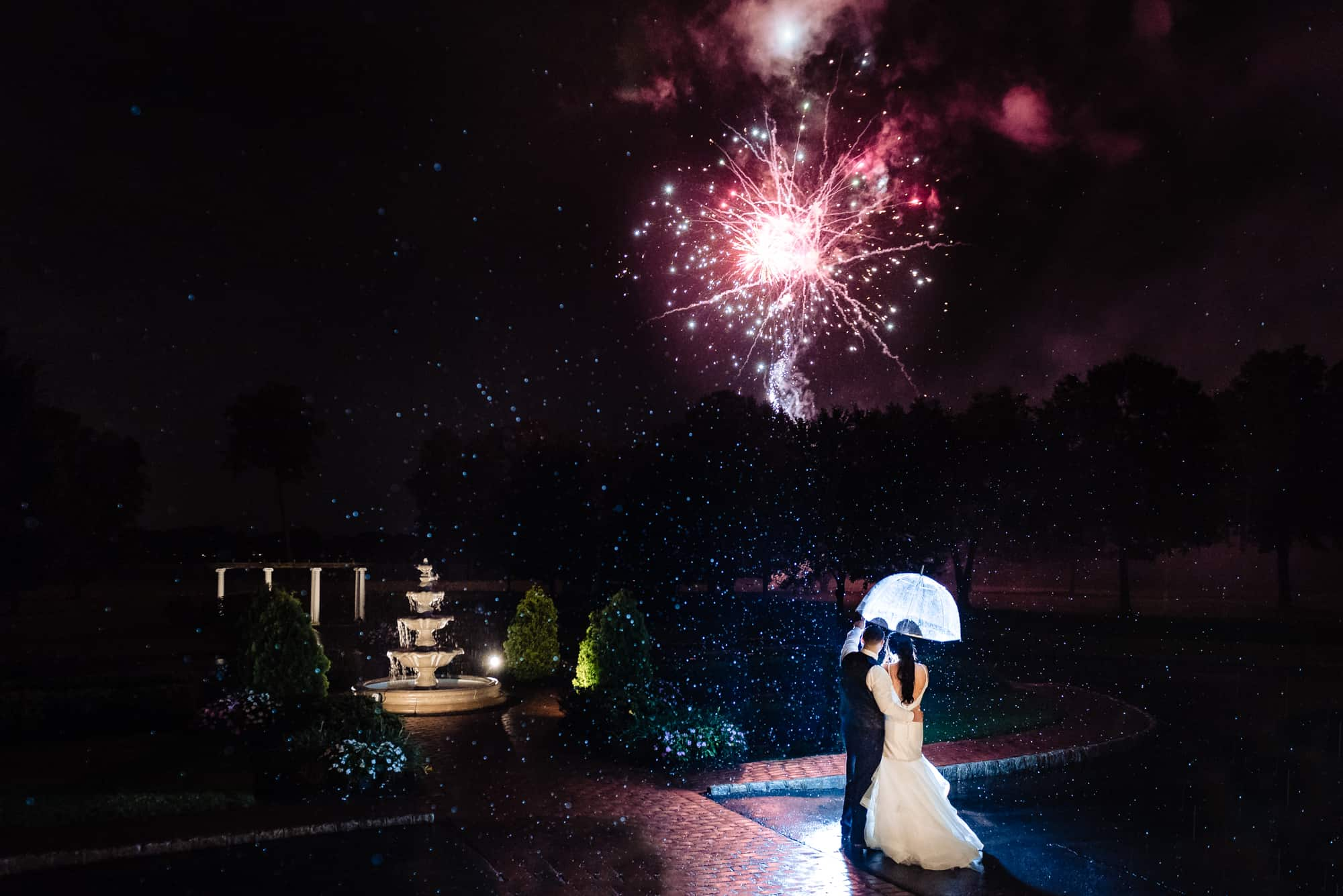 wedding day, bride and groom looking at red firework under an umbrella on a rainy night
