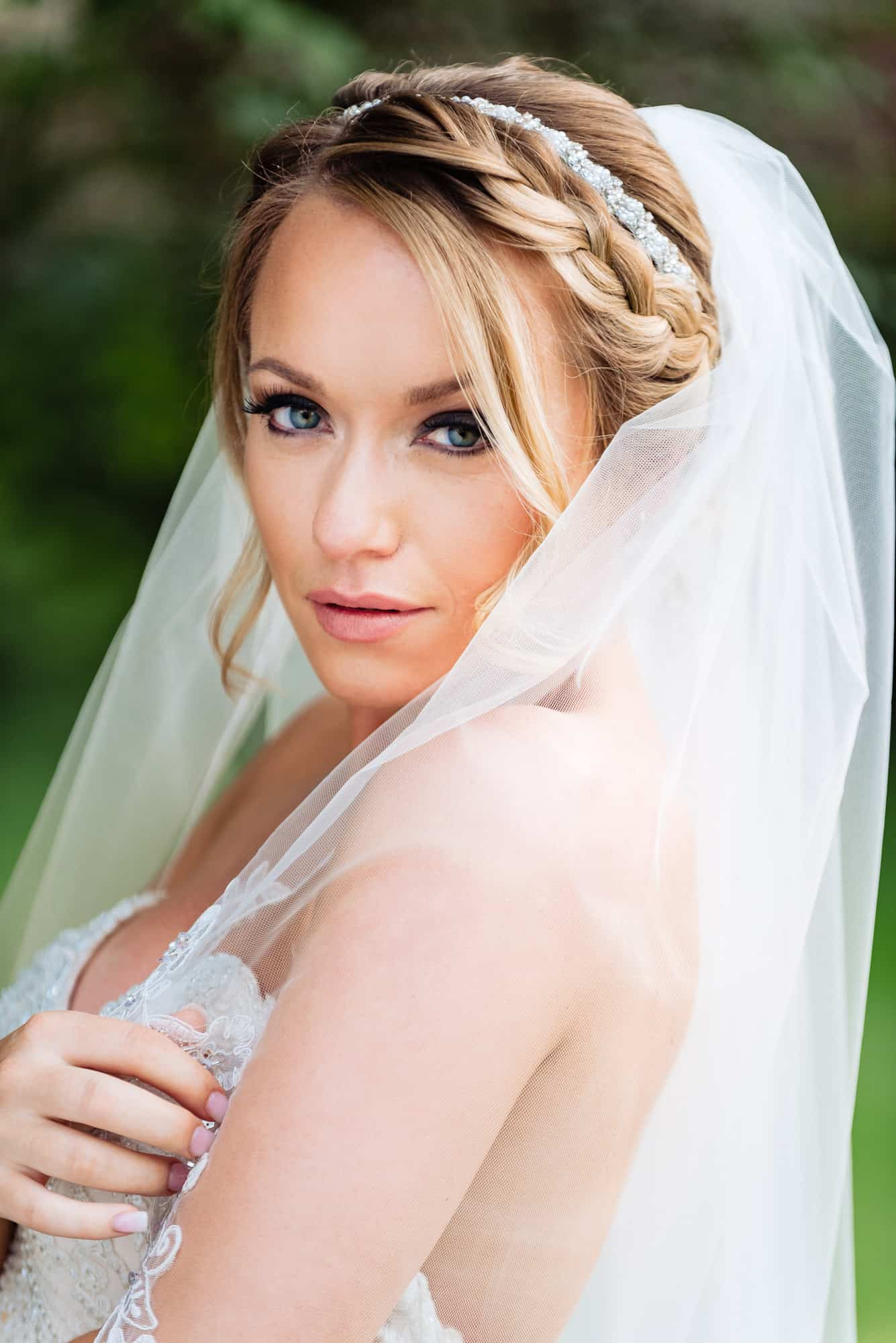 bridal photos, closeup of bride looking into camera covering up with veil