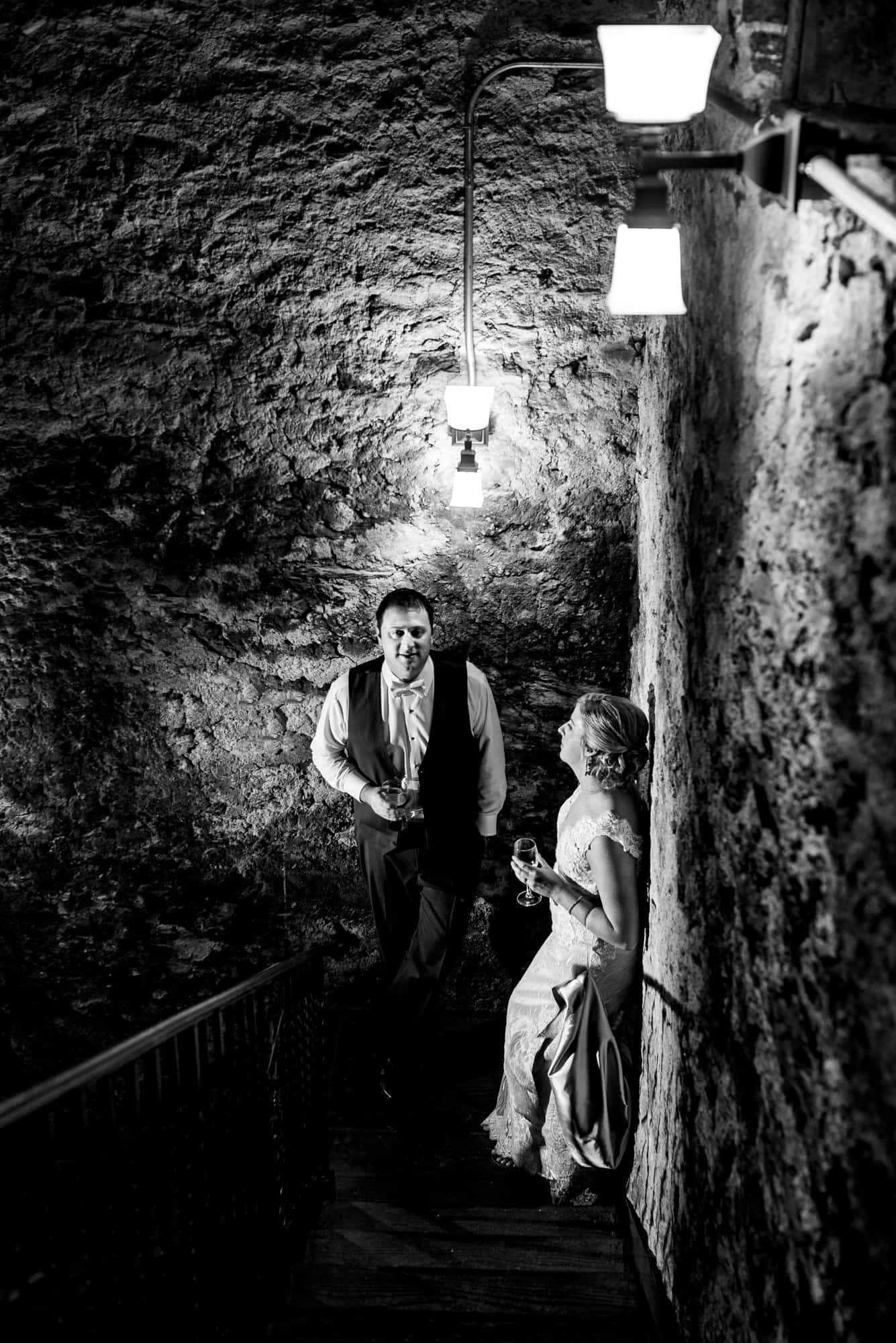wedding day, bride and groom talking in cellar while holding glasses of wine
