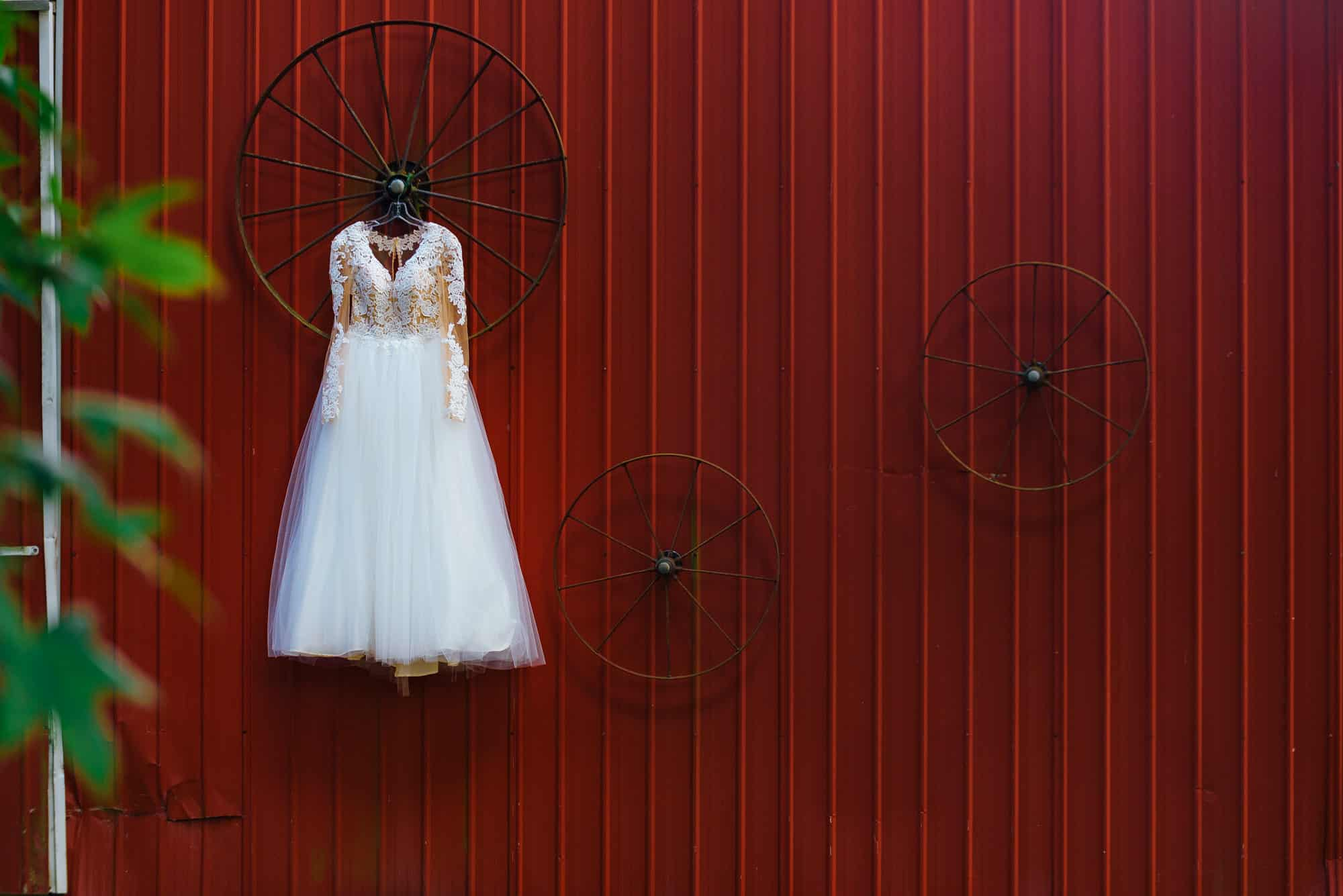 wedding dresses, dress hanging from red barn