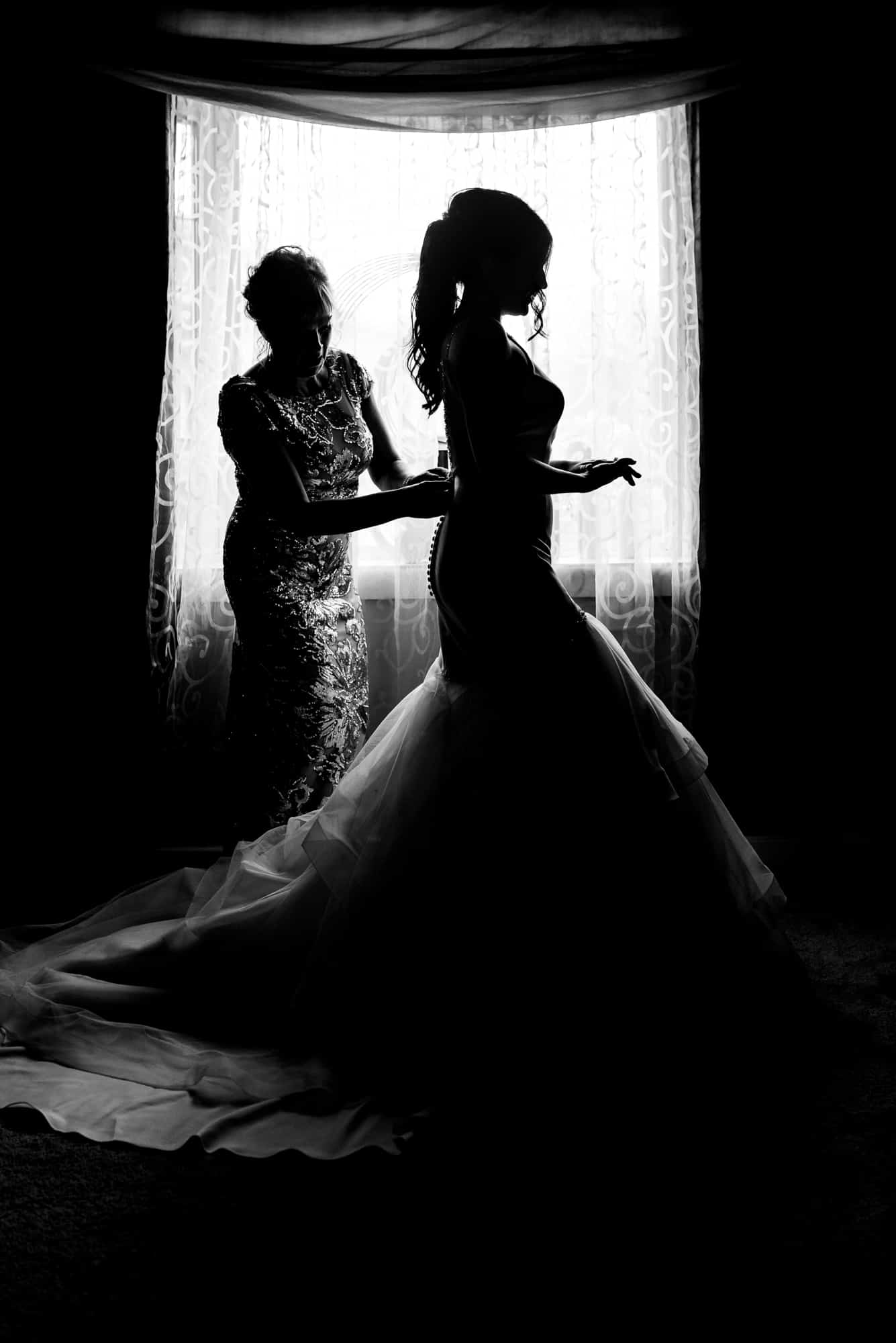 wedding morning, silhouette of mother helping bride get ready