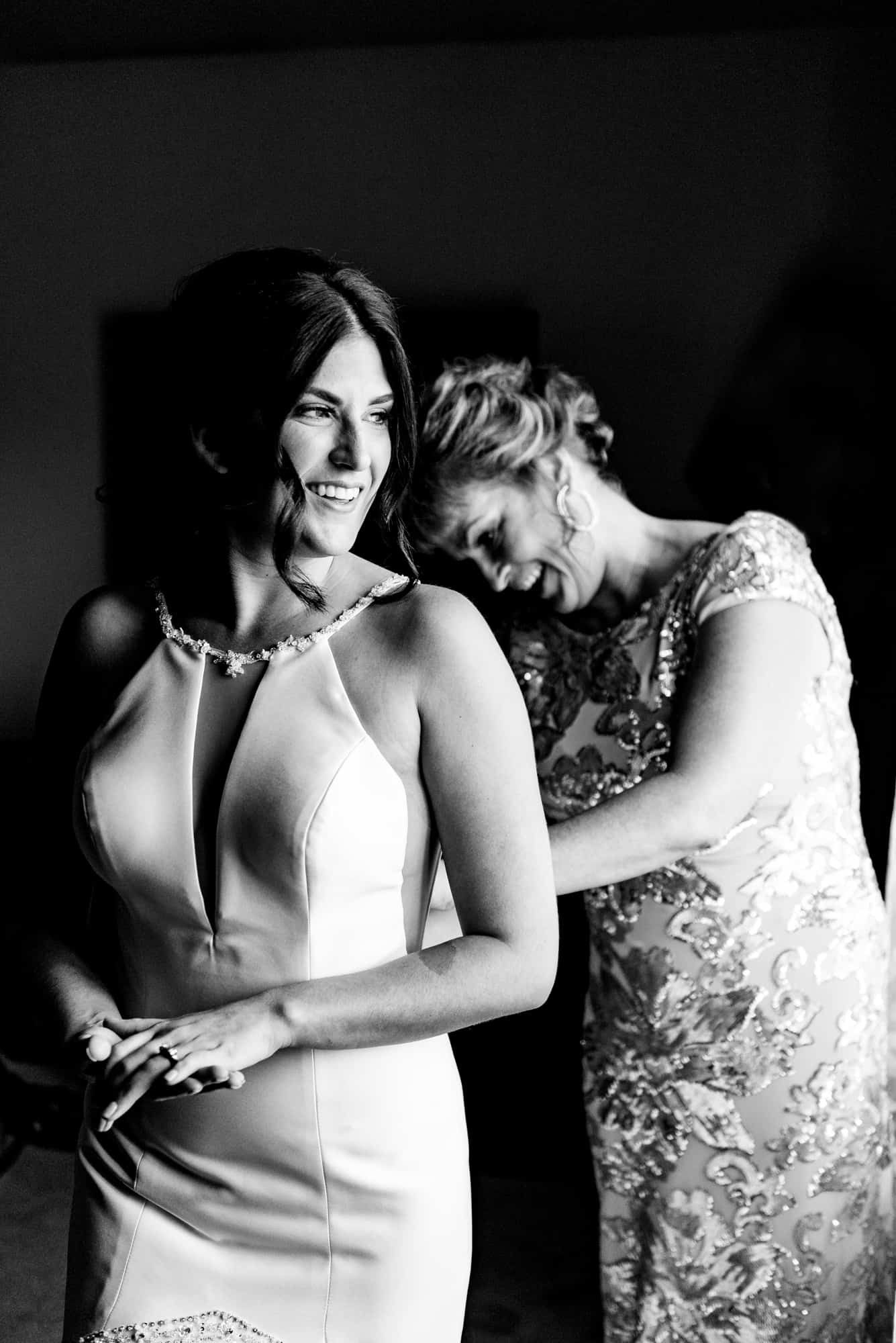 wedding morning, mother helping bride button back of dress, bride smiling