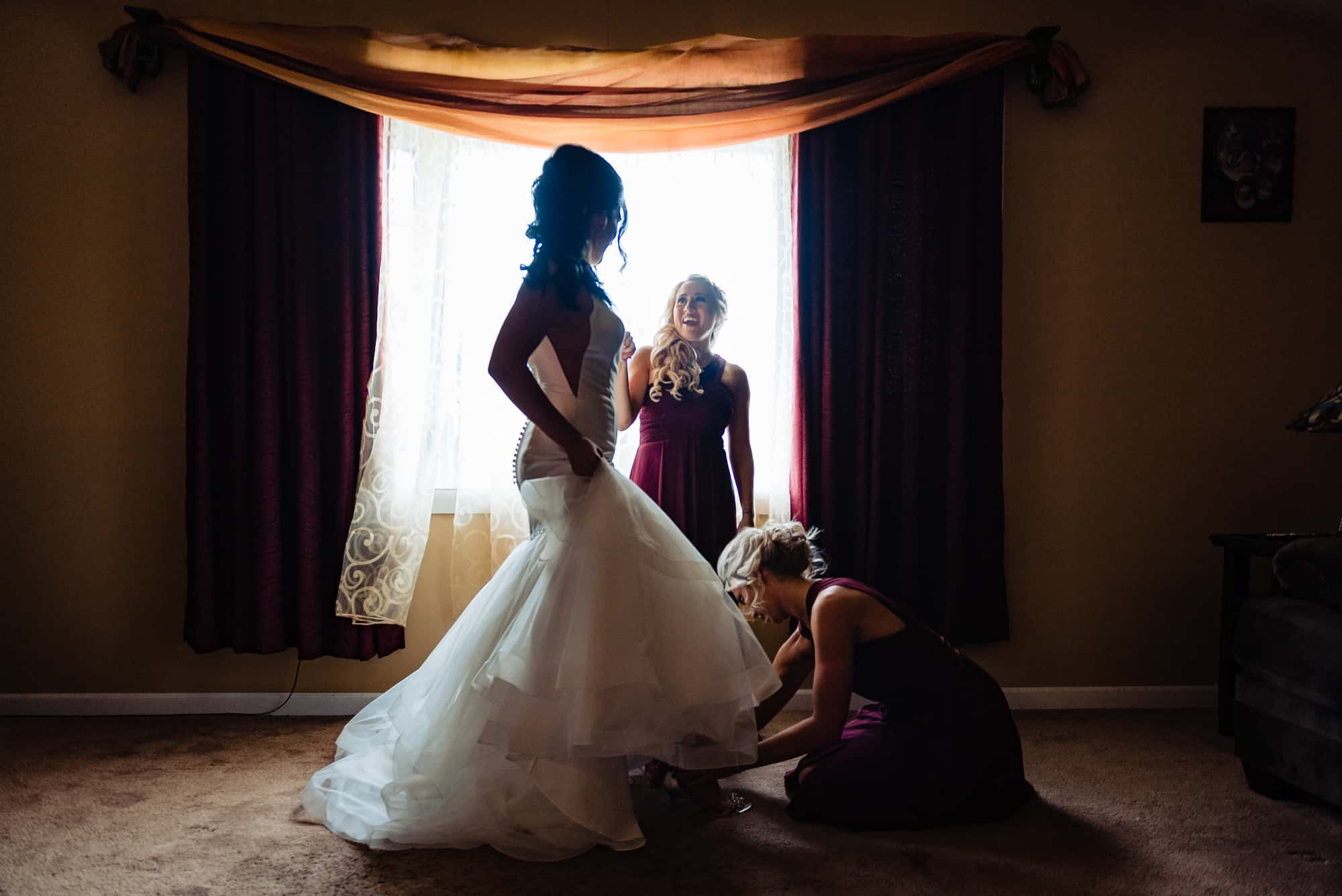 wedding morning, bridesmaids helping bride put on shoes