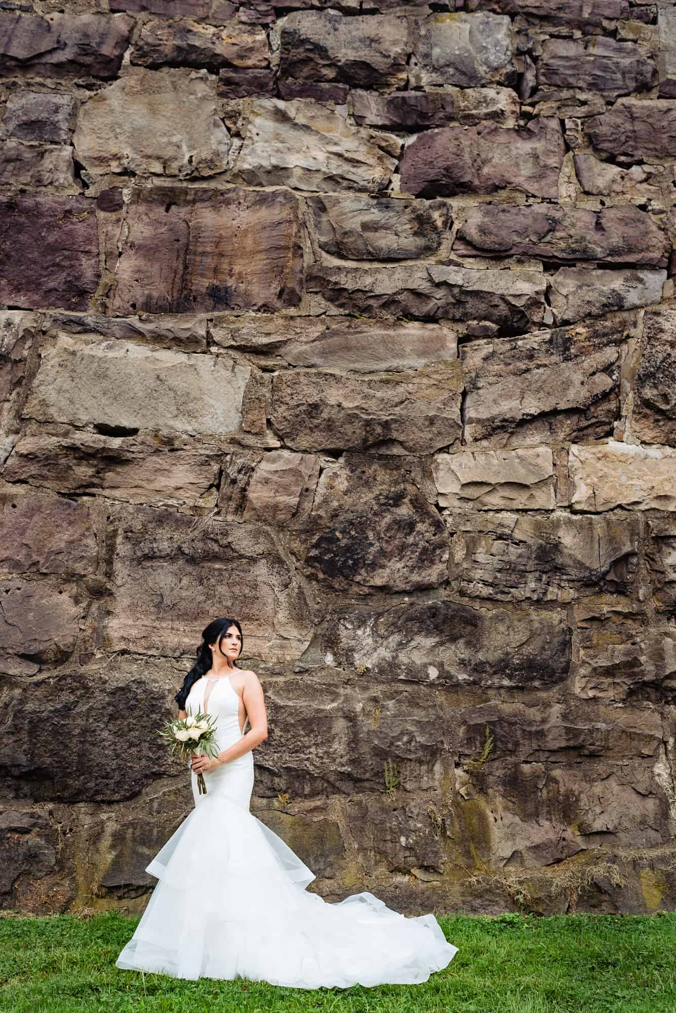 bridal photos, bride looking away from camera in front of prison wall