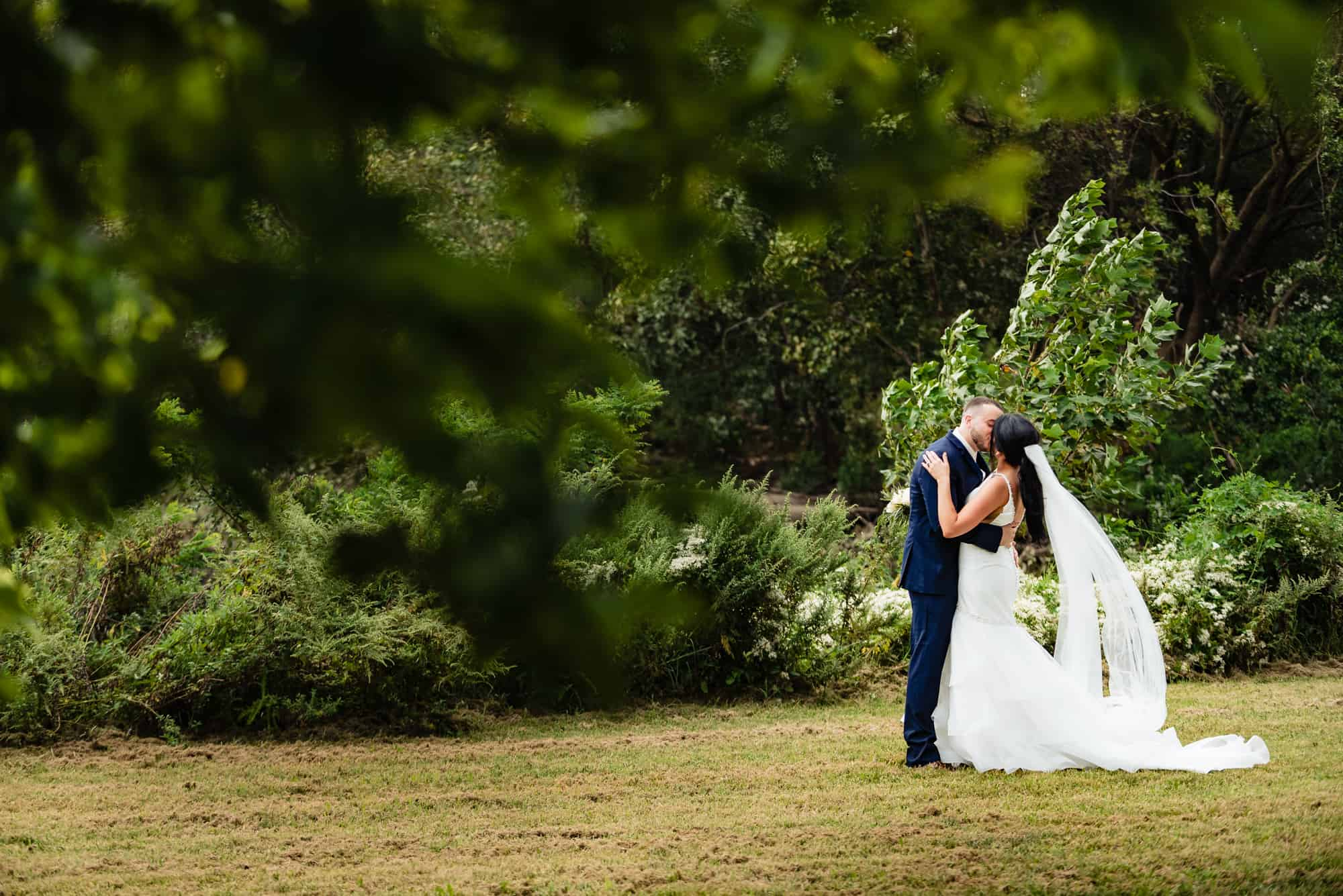 wedding day, bride and groom kissing outside behind bush
