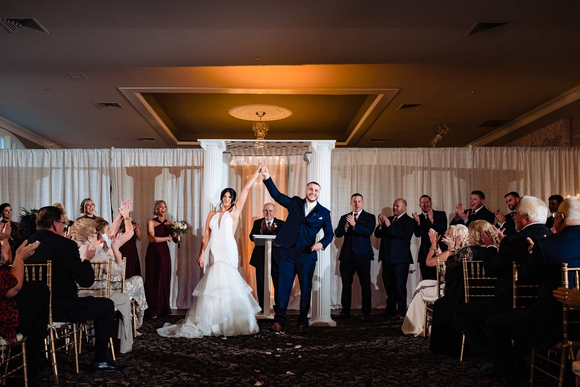 wedding ceremony, bride and groom holding hands in the air facing guests