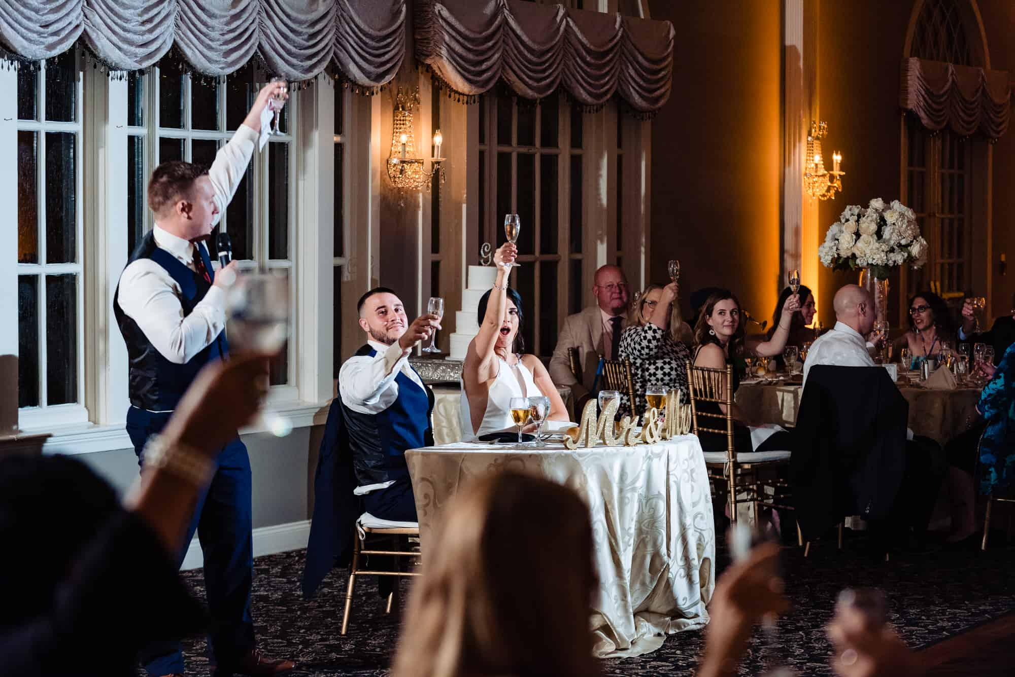 wedding reception, guests holding champagne glasses in the air for a toast