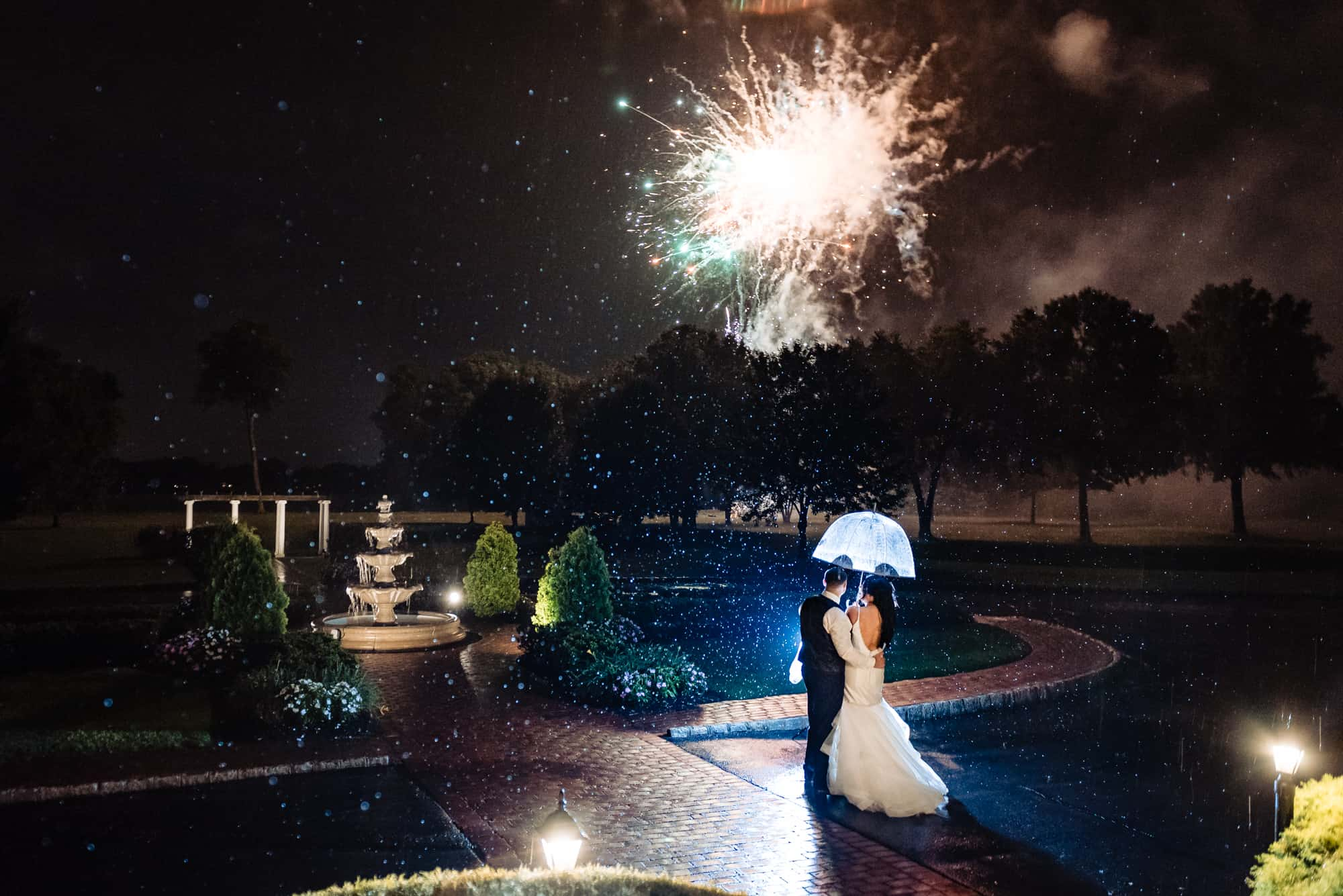wedding day, bride and groom embracing each other under an umbrella watching fireworks