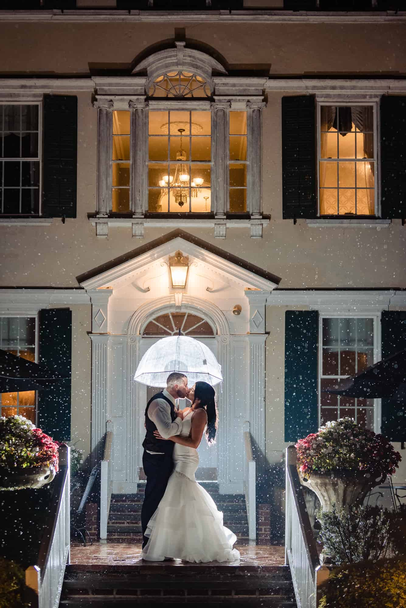 wedding day, bride and groom kissing under umbrella on rainy night