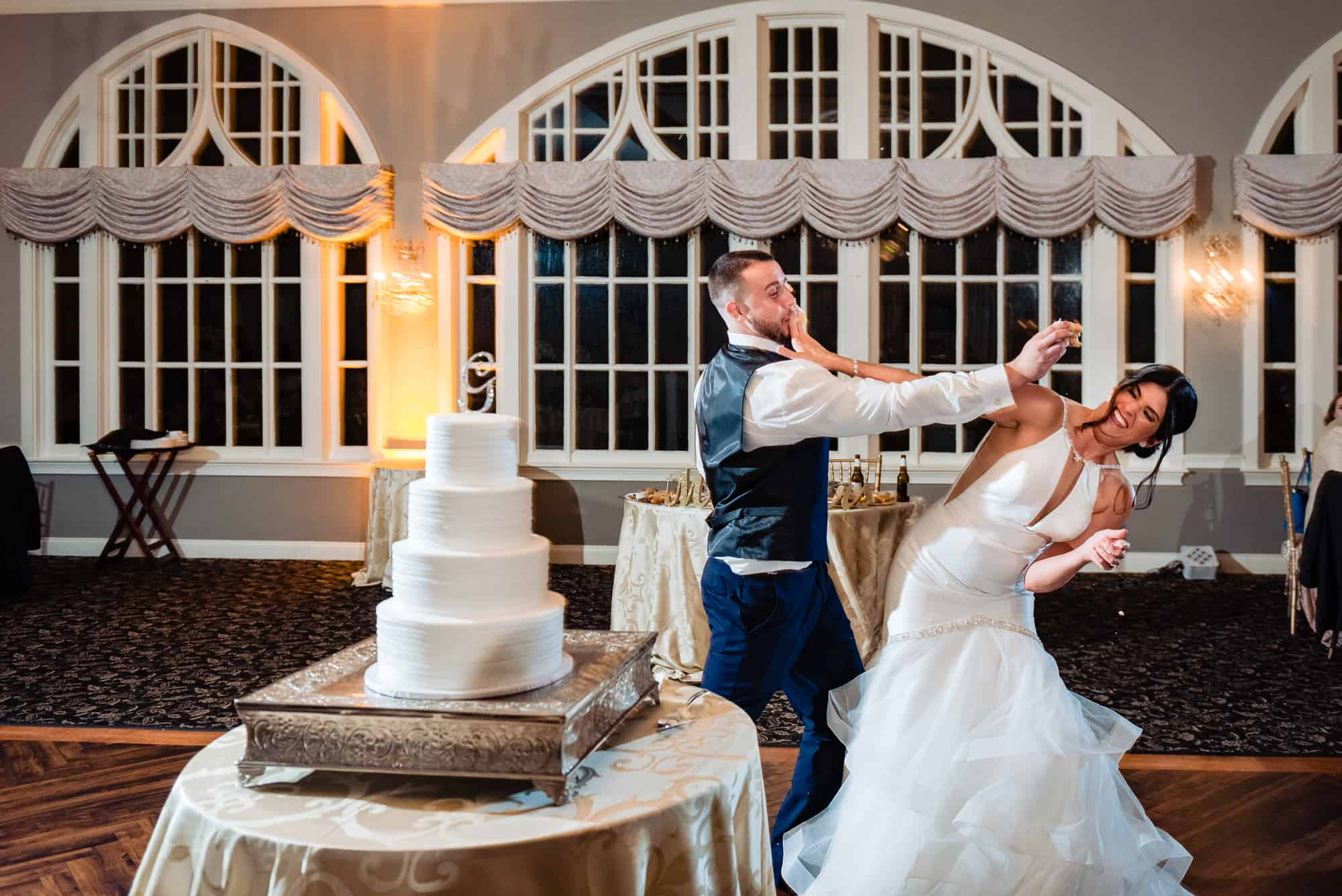 wedding day, bride and groom smashing cake in each others faces