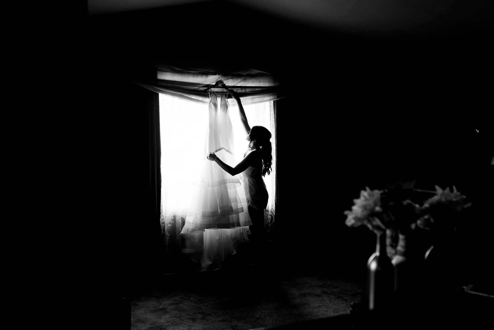 wedding morning, silhouette of bride handing gown in window