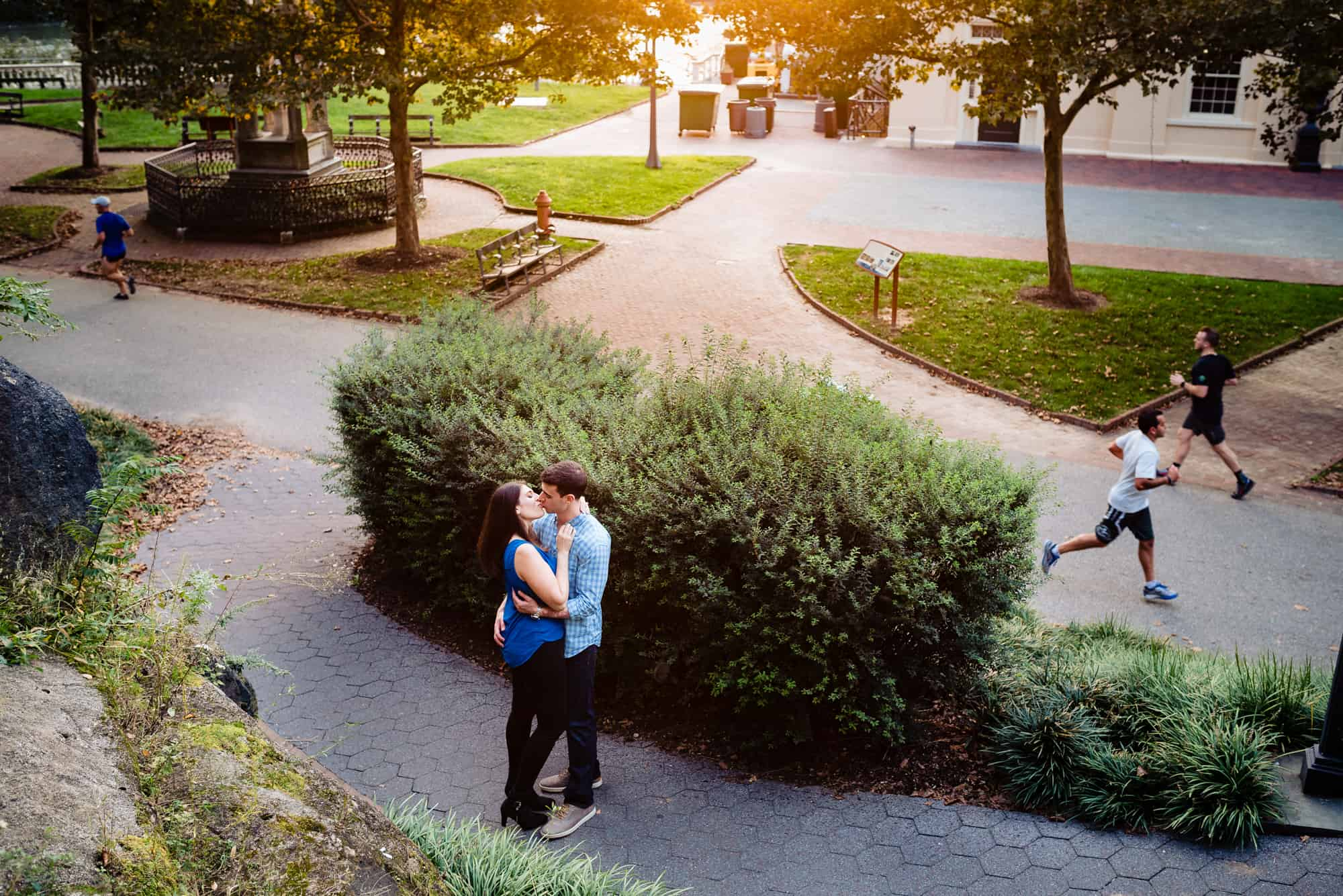 couple kissing behind bushes