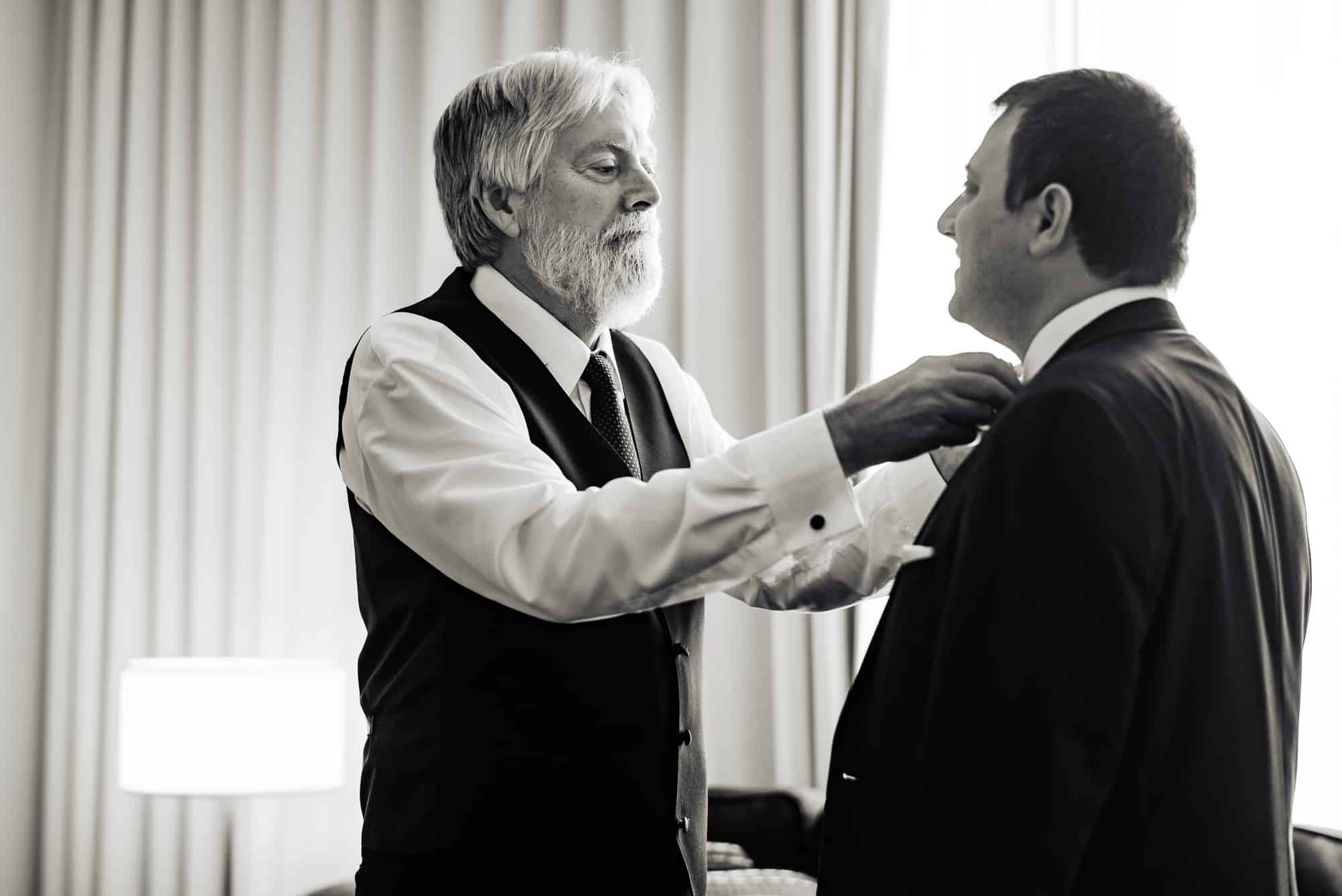 getting ready, father of the groom helping groom fix his tie