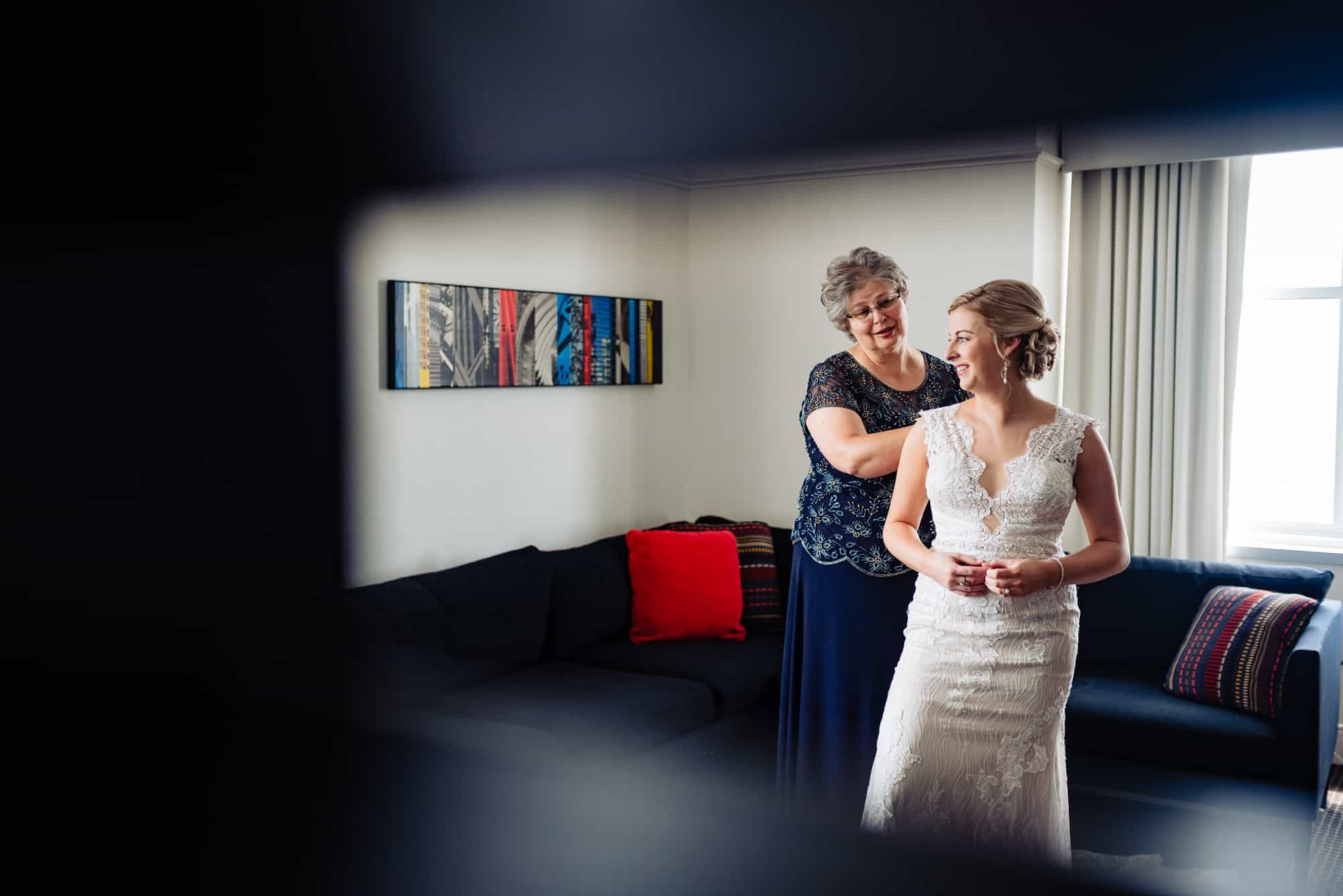 getting ready, mother of the bride helping the bride get into her Maggie Sottero lace gown