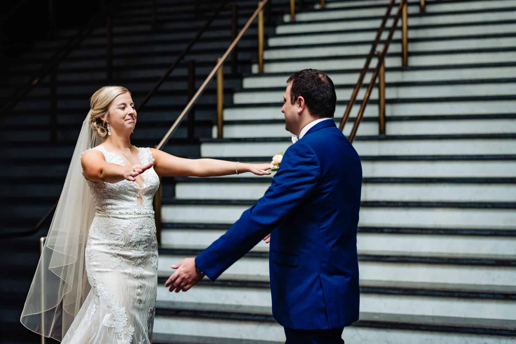 wedding day, bride and groom reaching for an embrace while smiling in a staircase