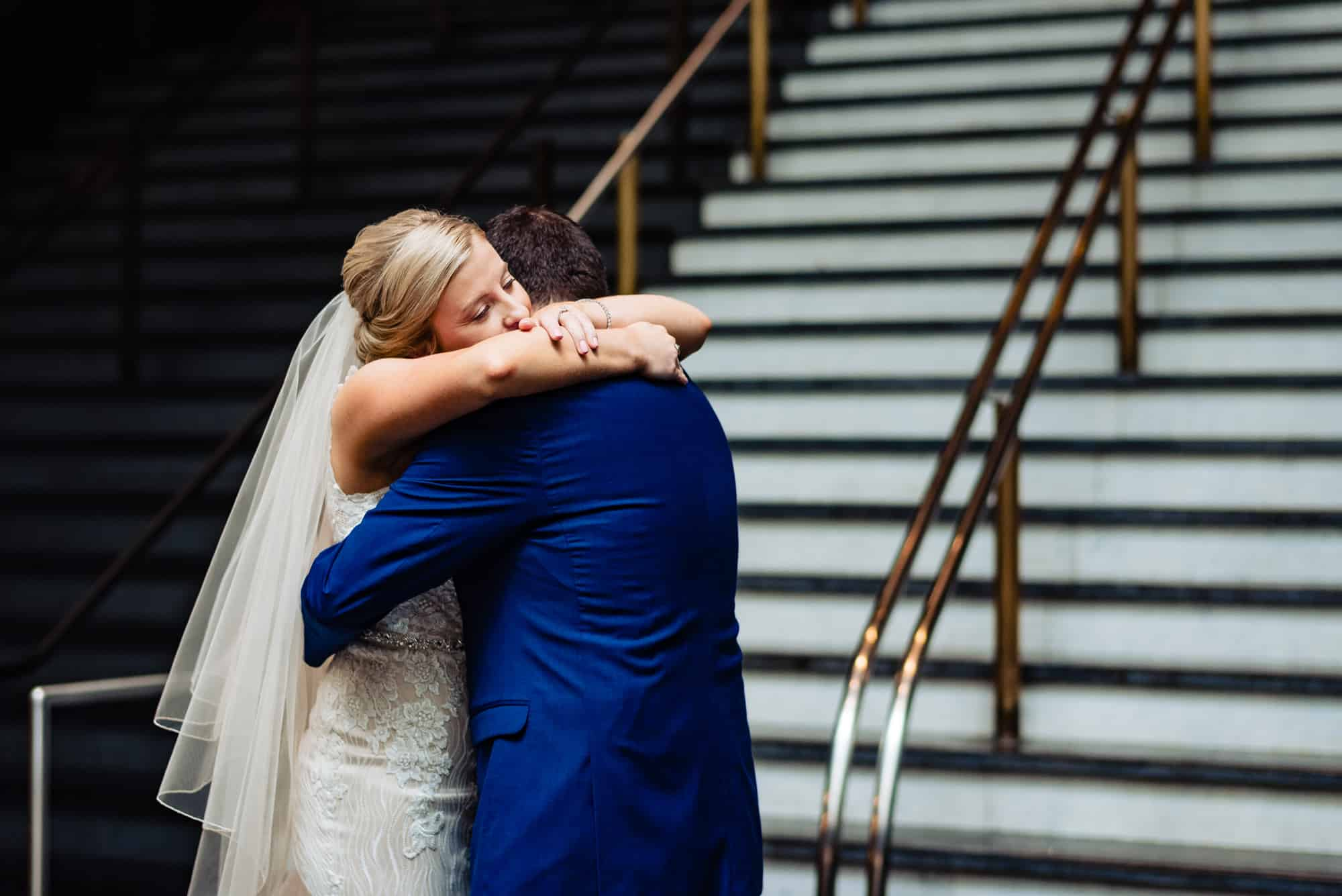 wedding day, bride and groom hugging each other tightly in a staircase