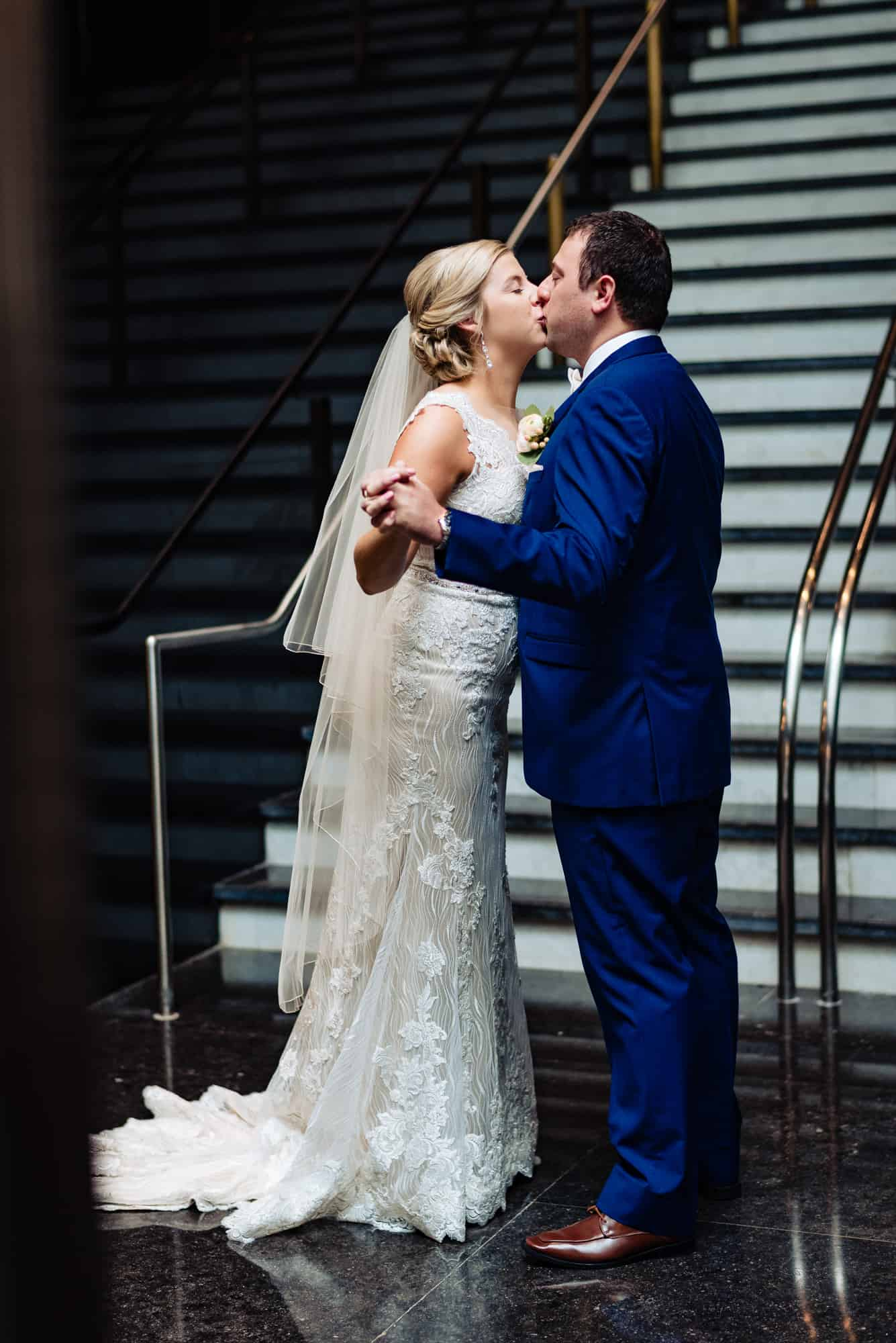wedding day, bride and groom kissing and holding hands in a staircase