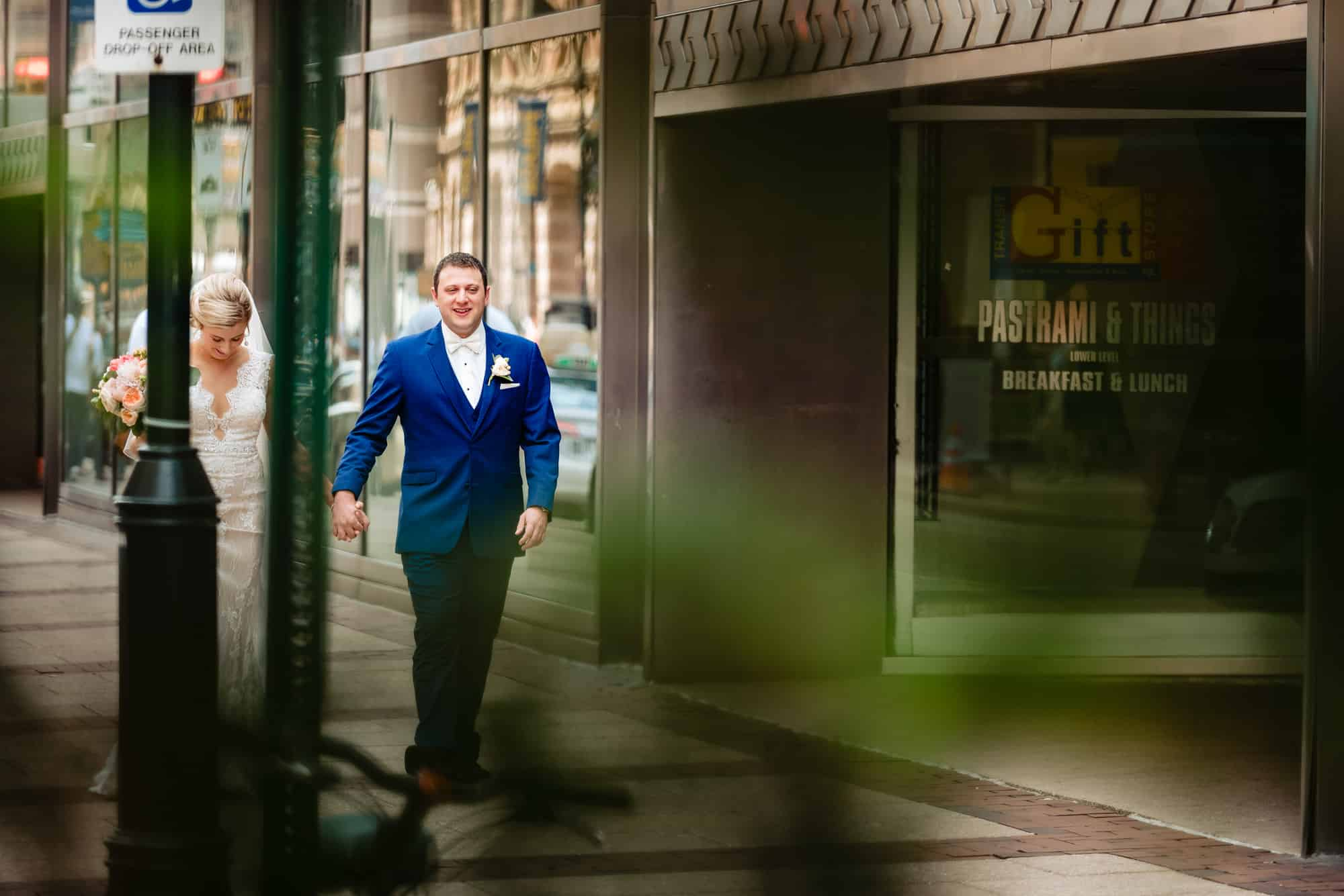 wedding day, photo thru bushes of bride and groom walking down the street