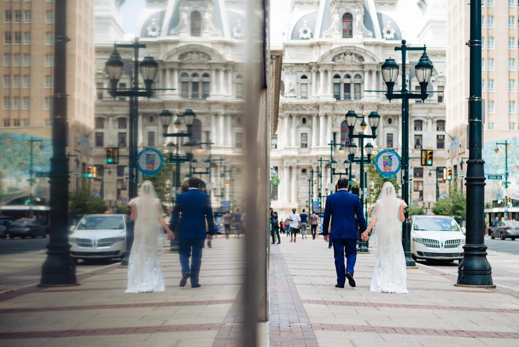 wedding day, far away back shot of the bride and groom holding hands walking down the sidewalk of Philadelphia in front of the William Penn building