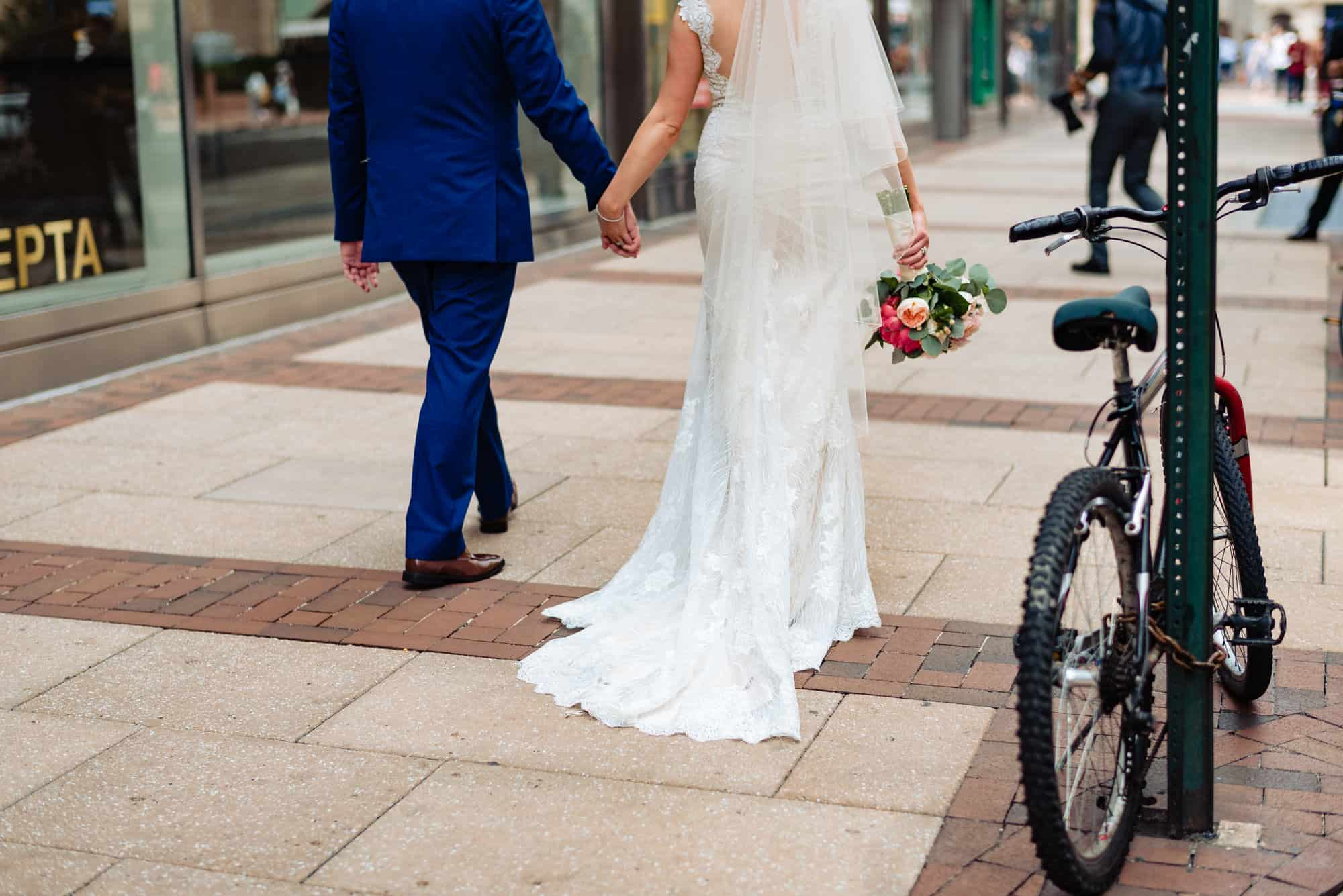 wedding day, the back of the bride and groom holding hands walking down the streets of Philadelphia